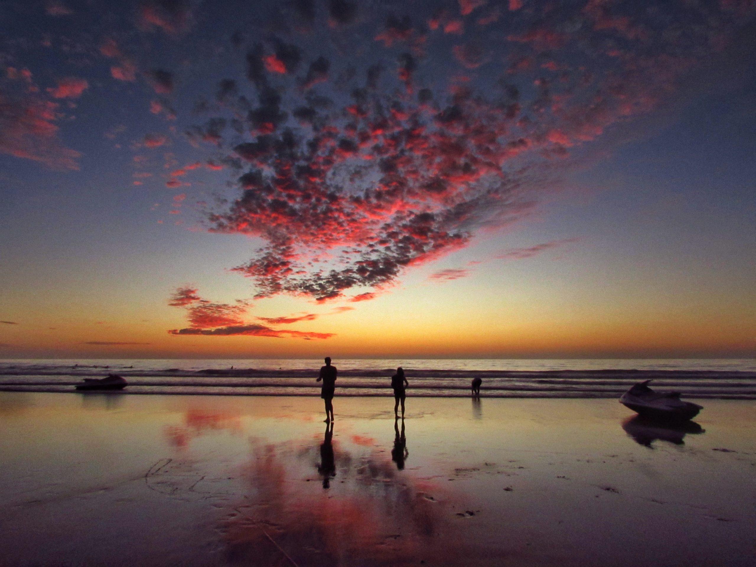 Foto de la playa con un atardecer y un par de personas