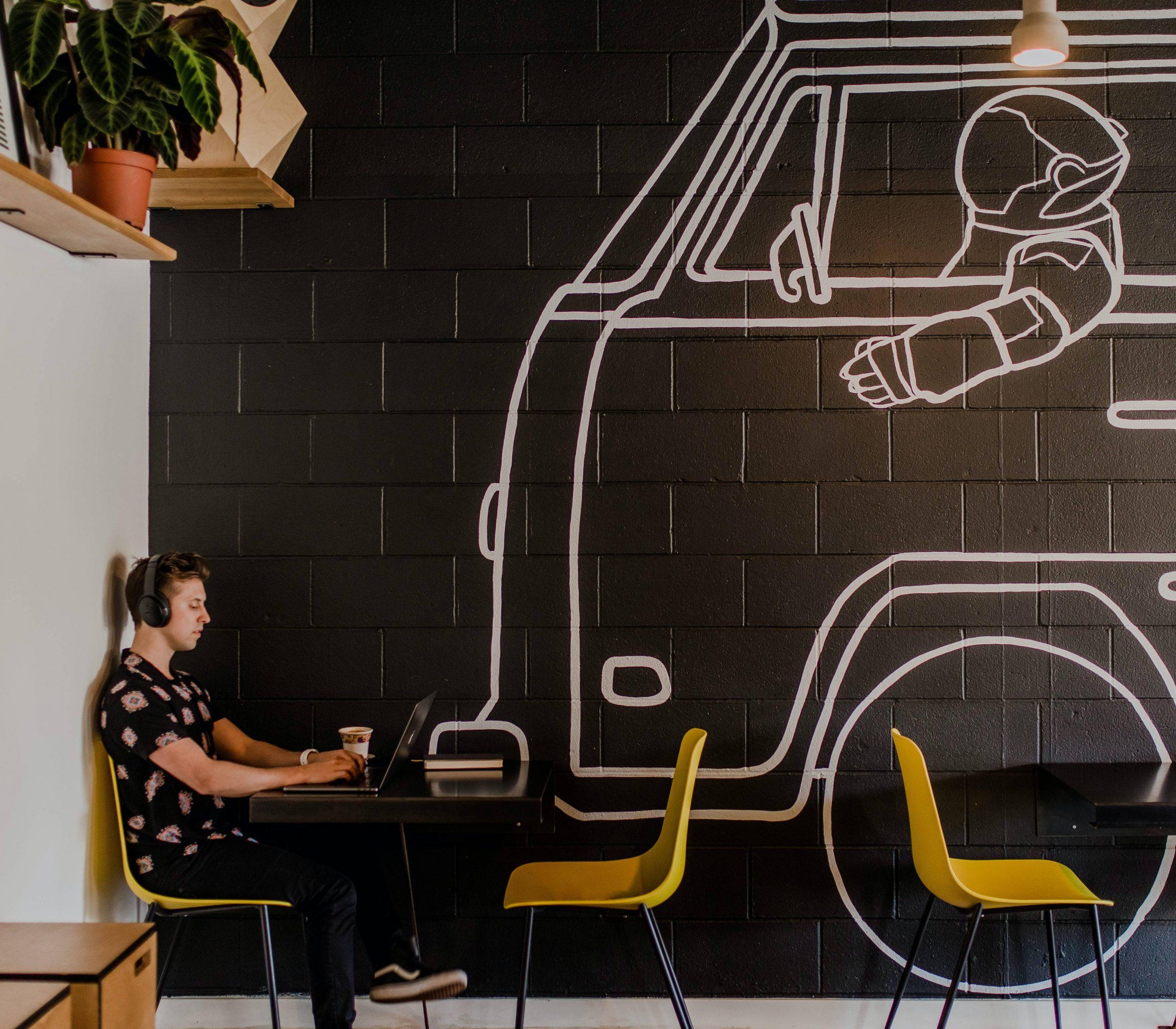 Nómada digital trabajando en café con un mural de una combi