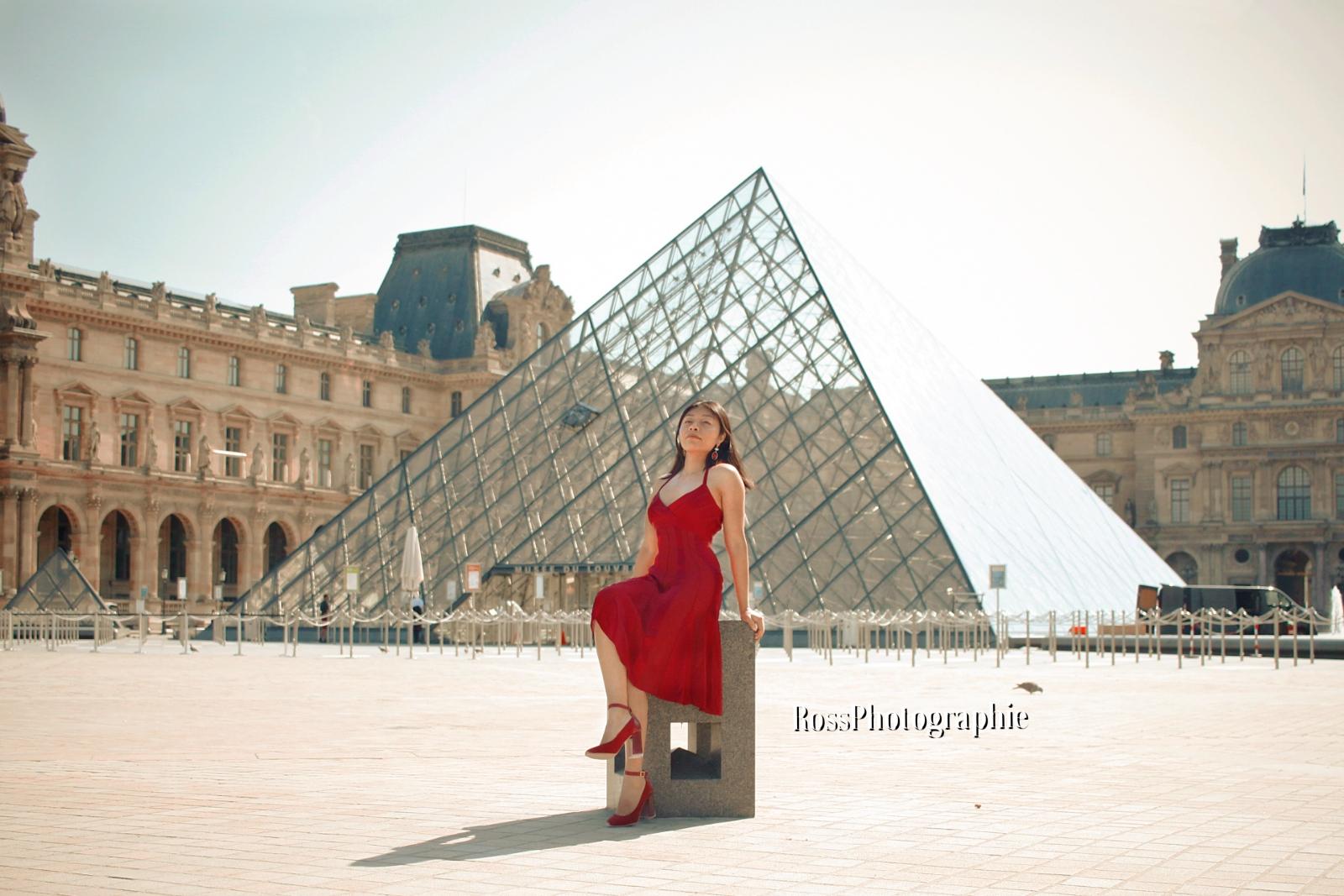 Chica frente a la piramide del mueo de Louvre
